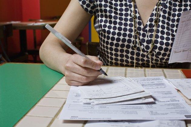 woman doing bills at restaurant