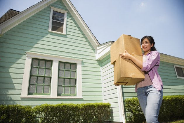 Hispanic woman carrying moving boxes outdoors