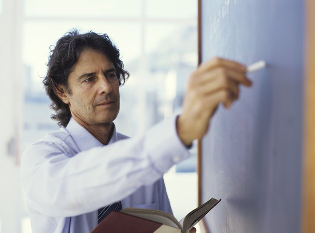 Teacher writing on blackboard and holding book, close up
