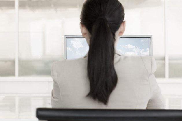 Businesswoman sitting in front of a computer with clouds and sky on the monitor