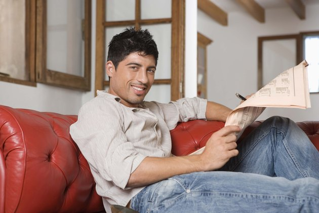 Man on sofa reading newspaper