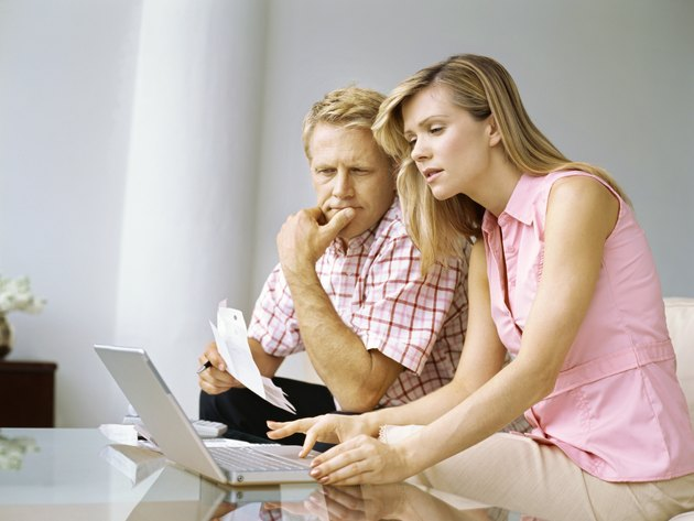 side profile of a mid adult couple looking at a laptop