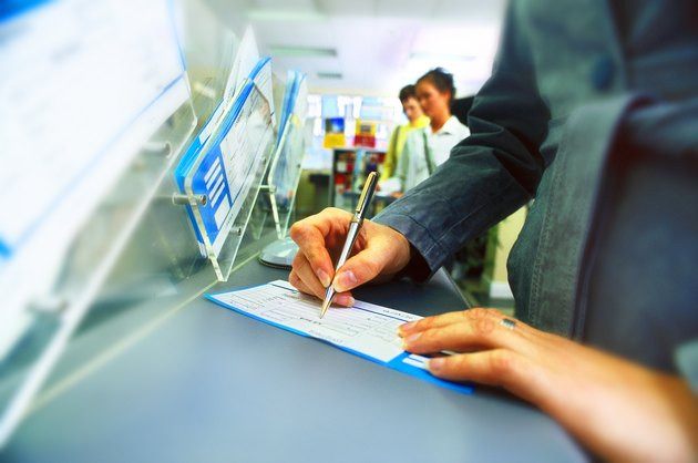 view of a woman filling a form at a counter