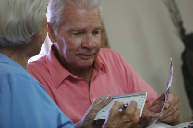 Close-up of a senior woman signing a check with a senior man sitting beside her