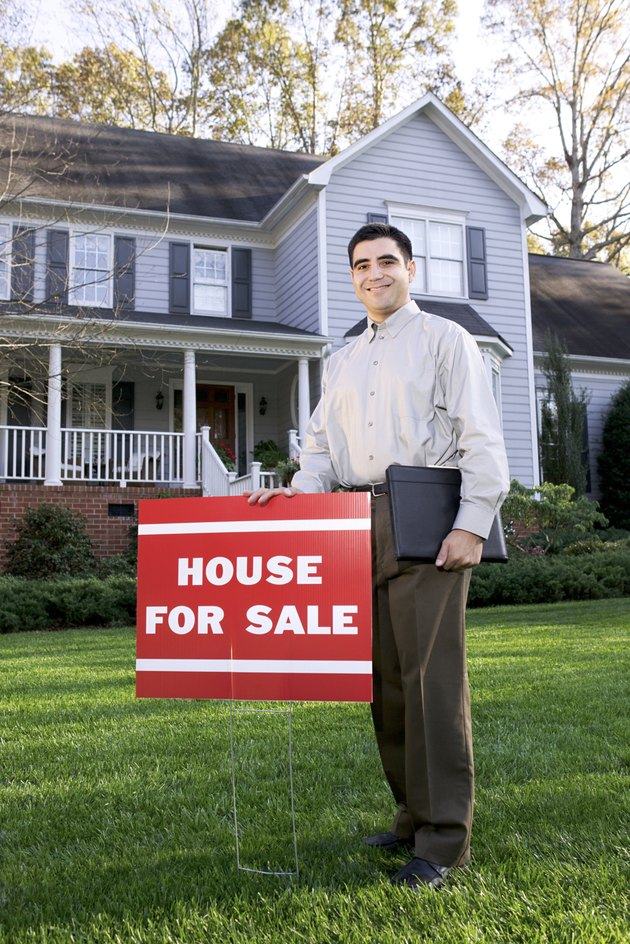 Man posing by house for sale sign