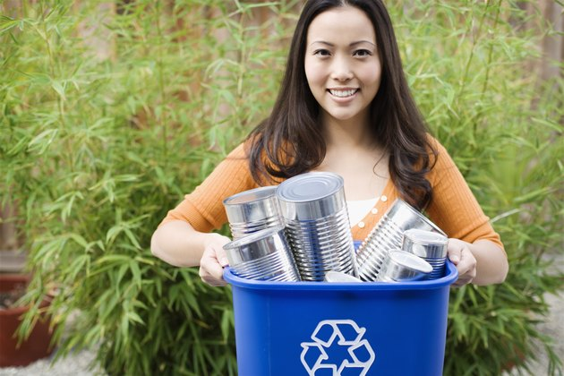 Smiling woman with recycling bin