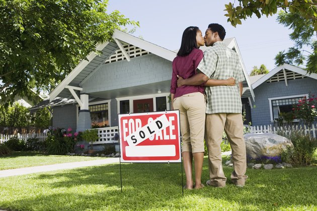 Kissing couple with sold sign and house