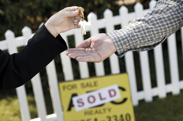 Hands of real estate agent handing over keys to new homeowner