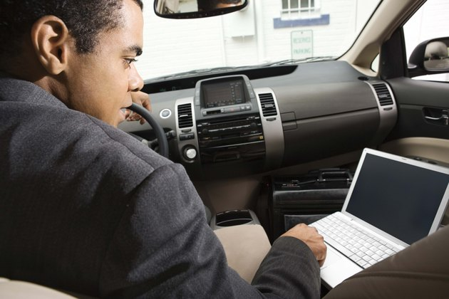 Businessman in car using laptop