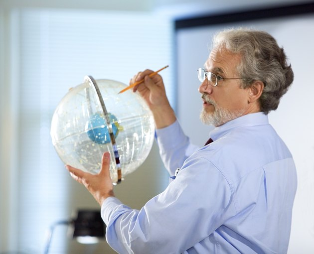 Professor holding astronomical globe