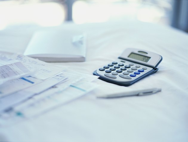close-up of bills with a calculator and a pen