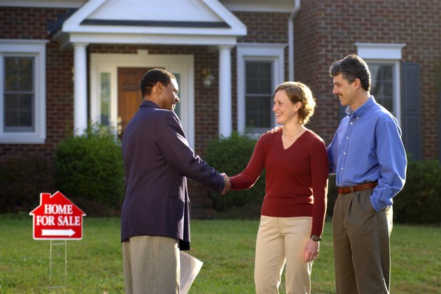 Couple and real estate agent shaking hands