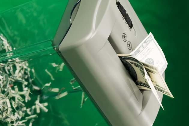 Twenty dollar bills going through a paper shredder