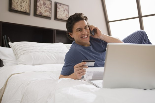 Man using cell phone in bed at home