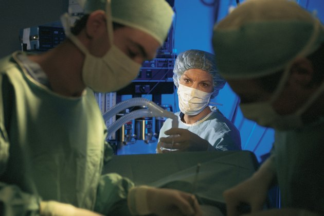 Anesthesiologist with others in operating room