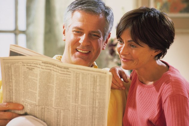 Couple reading newspaper stock listings
