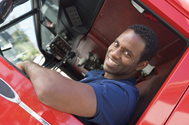A firefighter sitting in the cab of a fire engine