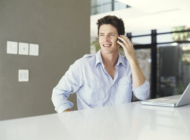 Man with laptop using mobile phone, smiling