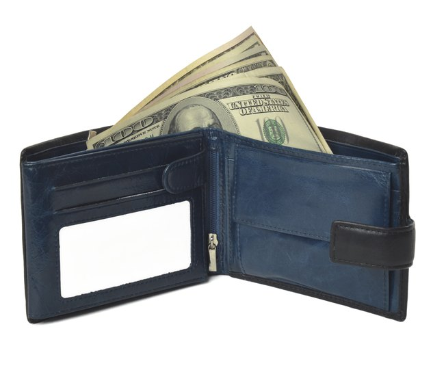 Blue purse with moneys (dollars) isolated on white background.