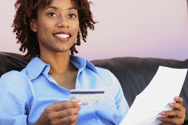 Close-up of a young woman holding a credit card and a bill