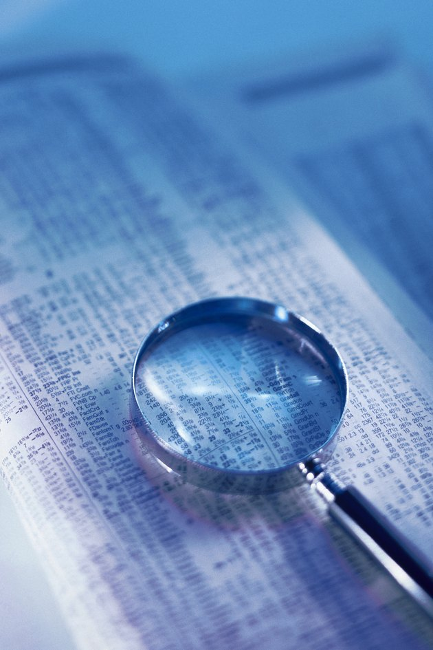 Magnifying glass on financial page of newspaper