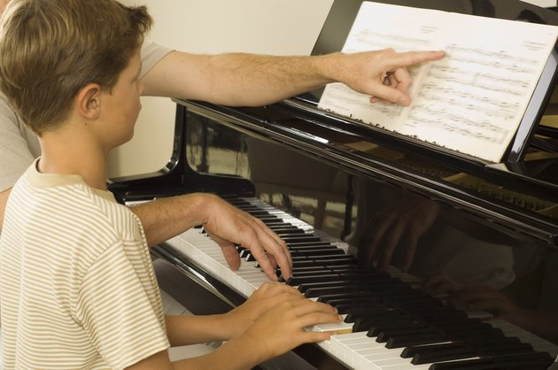 Instructor and boy playing piano