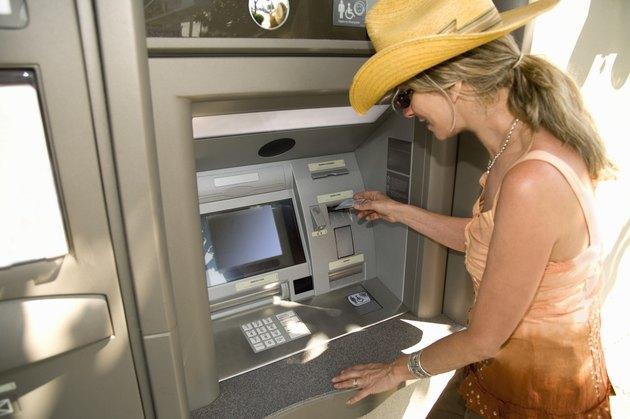 Woman using automatic teller machine