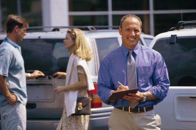 Car salesman on lot with couple