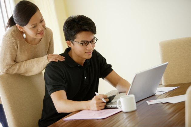 Woman looking over shoulder of man using laptop