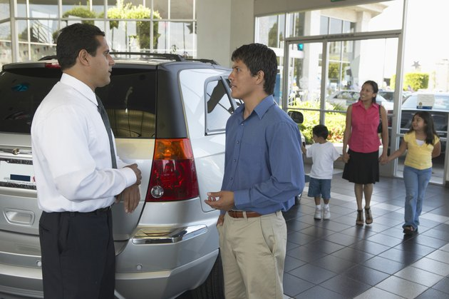 Man shaking car salesman's hand, family in background