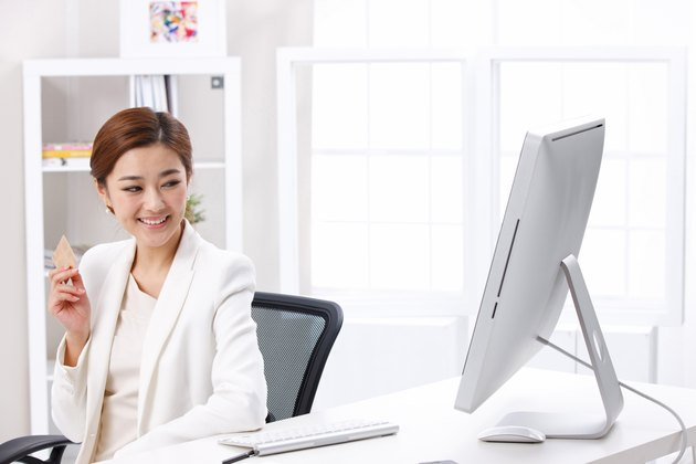 Young business lady holding credit card in front of computer