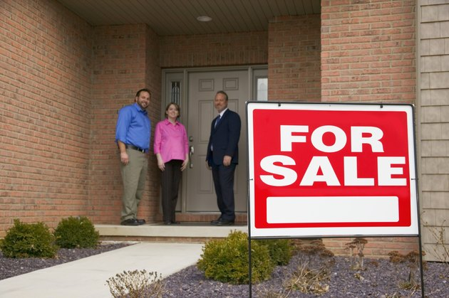 Couple and businessman in front of home, For Sale sign in foreground