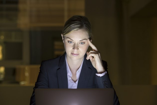 Businesswoman working late in her office on laptop, night light