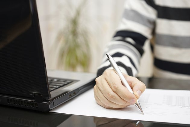 Man is writing document or studying with a laptop