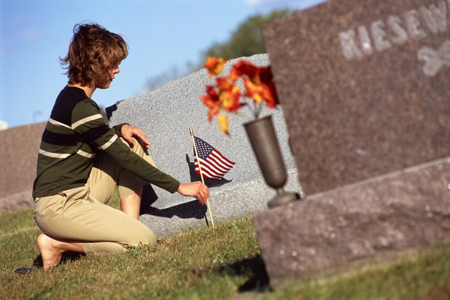 Woman placing flag by cemetery headstone