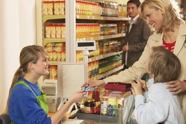 Mother with son (8-10) paying at supermarket checkout, smiling