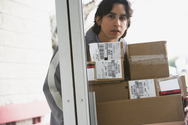 Male delivery person with stack of boxes