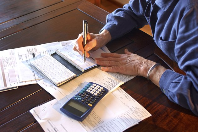 Close-up of a mature woman's hands as she sits at a table writes checks.