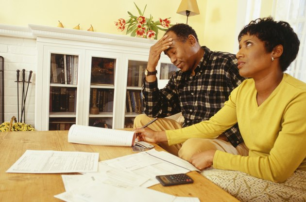 Frustrated couple calculating finances, side view