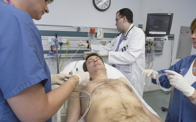 Doctors working on male patient in hospital