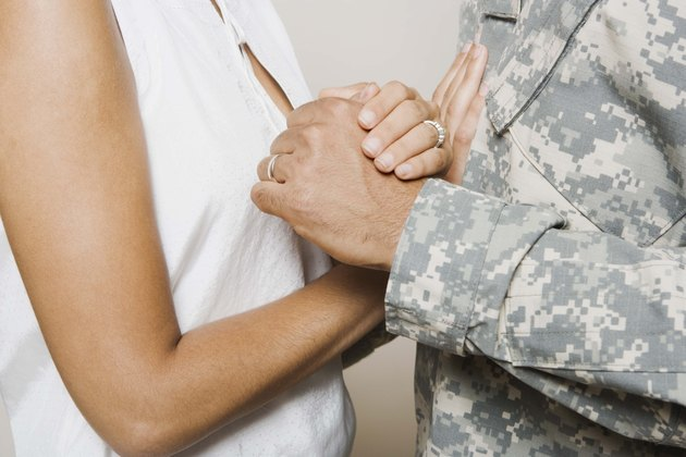 Woman and soldier holding hands