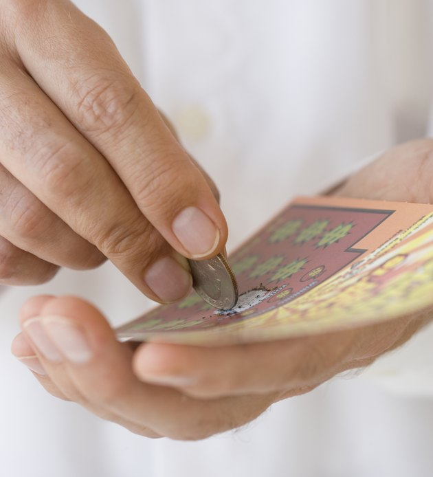 Man scratching lottery card with coin