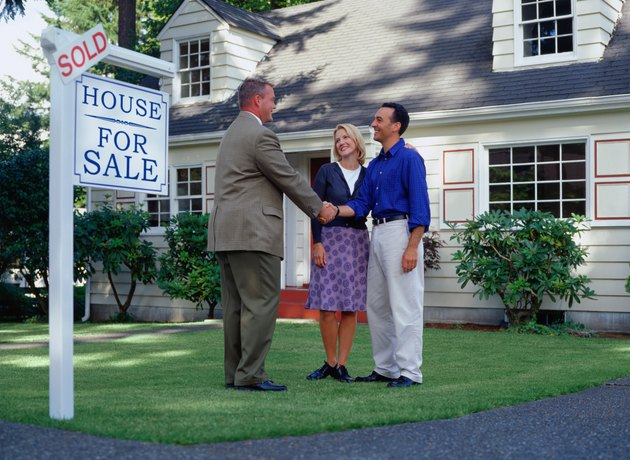 Real estate agent and couple standing in front of sold house