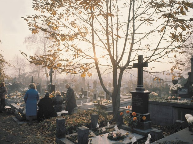 People at burial plot in cemetery