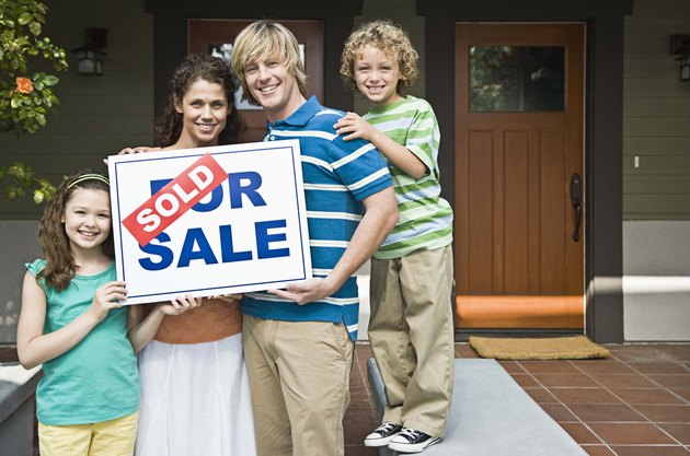 Family with house and sold sign