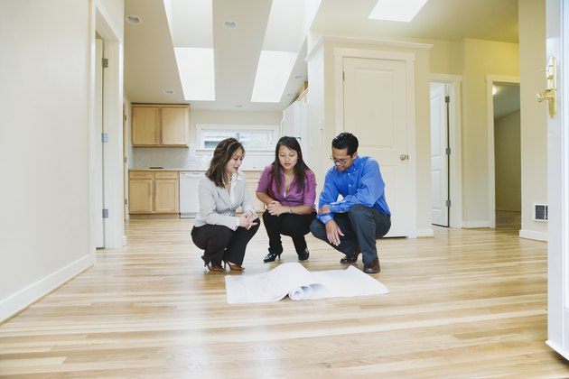 Female real estate agent looking at blueprints with couple in new house