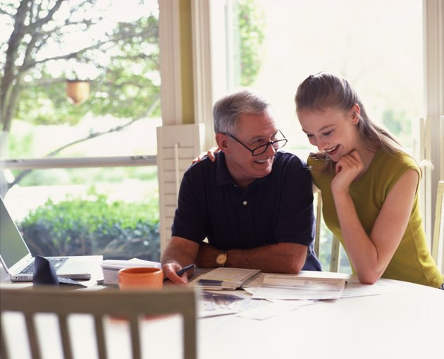 Girl with grandfather paying bills