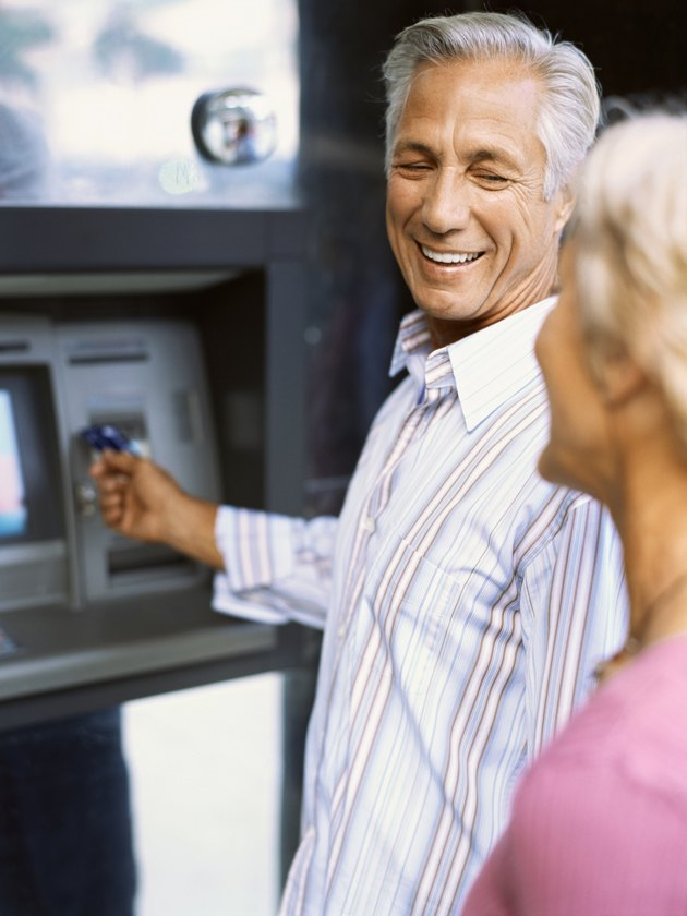 Side view of a mature couple at an ATM