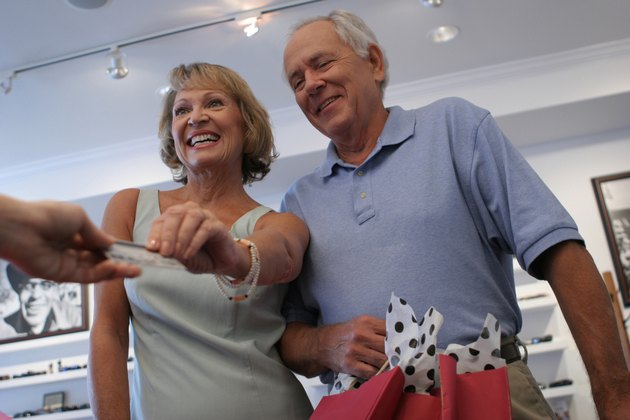 Low angle view of a senior couple handing a credit card to a person