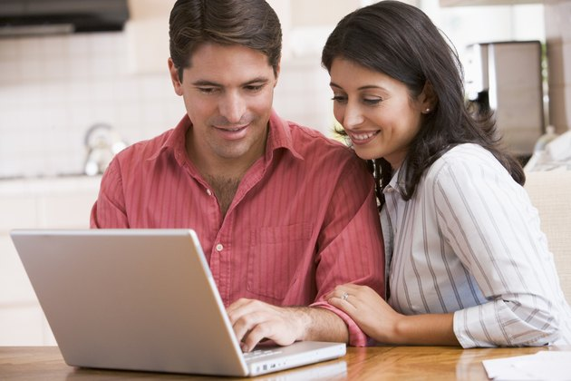 Couple in kitchen with laptop smiling